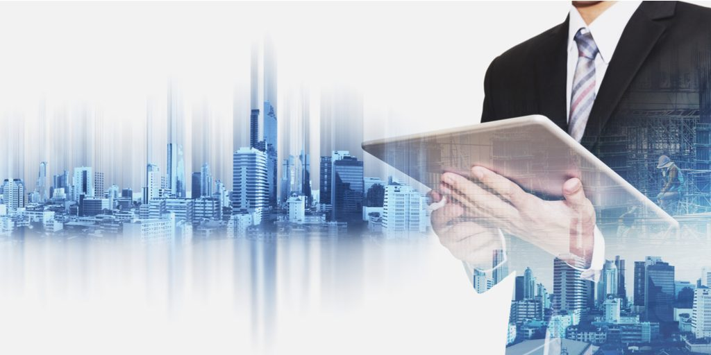 Businessman holding a tablet with composited city skyline behind him
