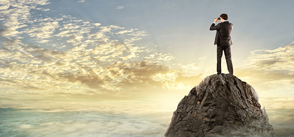 Businessman standing on a cliff looking into horizon for opportunities