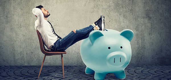 Businessman sitting back with legs on large piggy bank