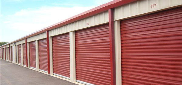 Self storage building exterior with red doors