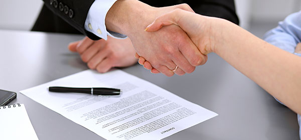 Two people shaking hands with a signed contract