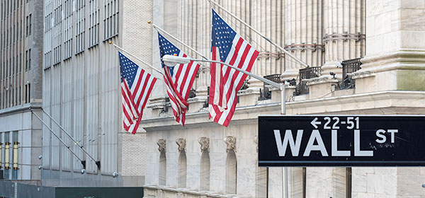 Wall street sign with building and flags